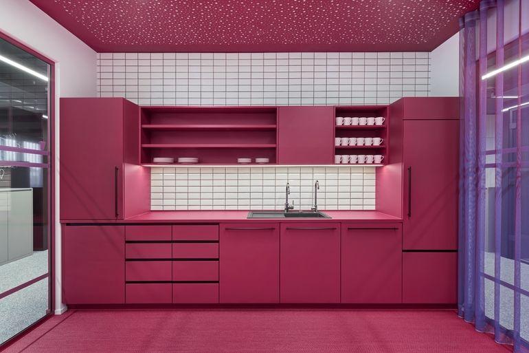 Eine pinke Küche mit perforierter Decke für gute Raumakustik