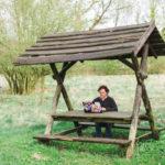 Mann sitzt auf einer Bank im Grünen