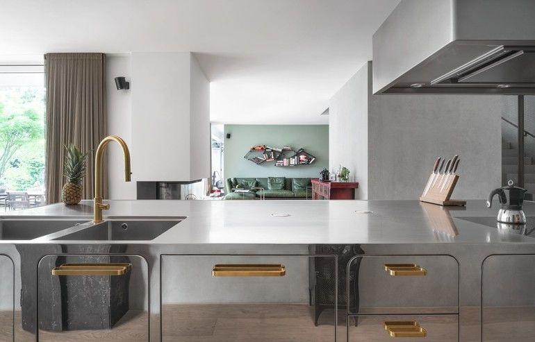 Arbeitsplatte aus Edelstahl mit eingelassener Spüle und Blick ins Wohnzimmer