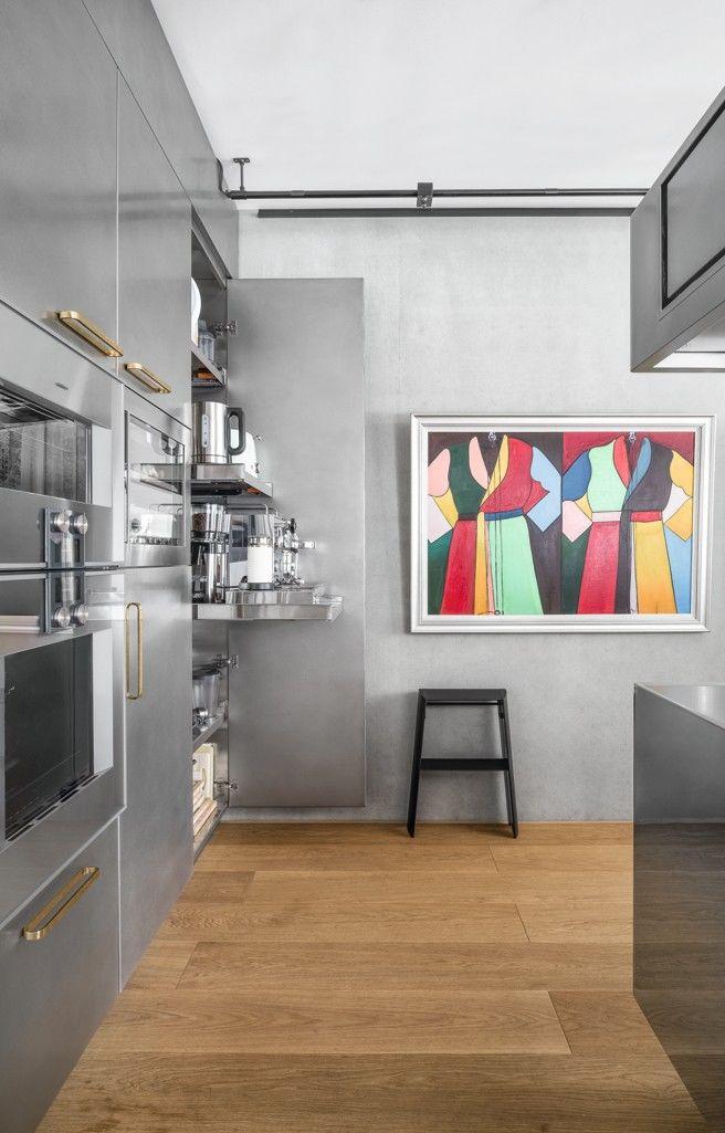 Edelstahlküche mit verborgenen Elektrogeräten und einem modernen Gemälde