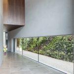 Die großzügige Verglasung des Foyers ermöglicht einen Blick auf die Grünwände des Innenhofs. Foto: Patricia Parinejad
