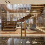 Über die ausladende Nussbaumholz-Treppe mit einer Umrandung aus raumhohen Kupferrohren gelangen die Gäste von der Eingangshalle in die oberen Geschosse. Foto: Patricia Parinejad