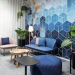 Besprechungsinsel mit Pflanzen, Sofa, Tischen und blauer Wand