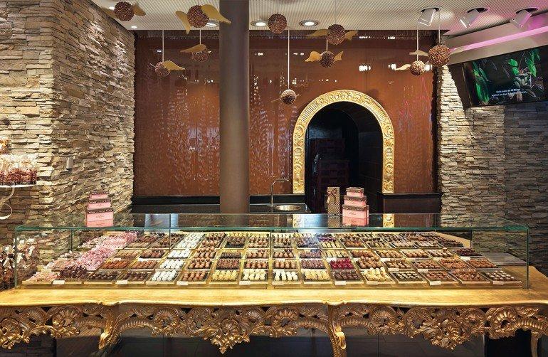 """Die """"Wall of Chocolate"""" bei Confiserie Bachmann, Luzern, im besonders warmtonigen Licht. Architektur: Marc Jöhl"""
