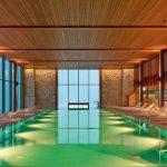 Das Herz des Spa-Bereichs im Hotelkomplex Bürgenstock ist der Indoor Pool. Über dem Wasser und den Ruhebereichen plante Licht Kunst Licht keine direkte Beleuchtung. Streiflicht macht auf die Textur der Steinwände aufmerksam. Foto: Johannes Roloff