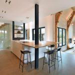Um einen Küchenblock aus weißer Himacs Mineralwerkstoff Arbeitsplatte stehen schwarze Stühle.