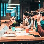 Group_of_people_with_VR_headsets_on_a_business_meeting