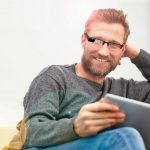 Young_man_wearing_smart_glasses_sitting_at_home_with_a_digital_tablet_smiling